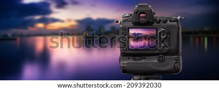Dslr camera shooting on a cityscape sunset with sea reflection - stock photo