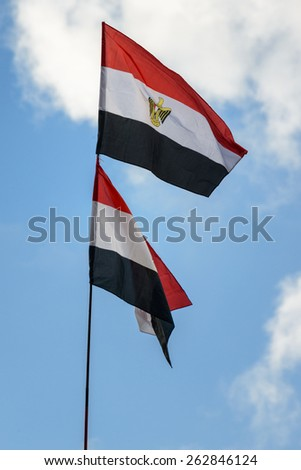 Dual Egypt Flags Raised over Blue Sky - stock photo