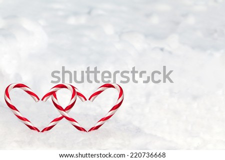 Dual heart-shaped candy canes in the snow with copy space. - stock photo