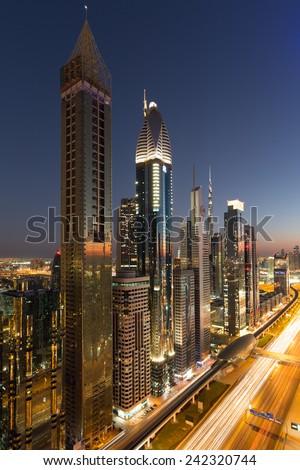 Dubai by night. Twilight. Burj Khalifa background. Sheikh Zayed Road skyscrapers. Dubai construction. Dubai skyscrapers and skyline.Ahmed Abdul Rahim Al Attar Tower.Dusit Thani. Rose Rayhaan by Rotana - stock photo