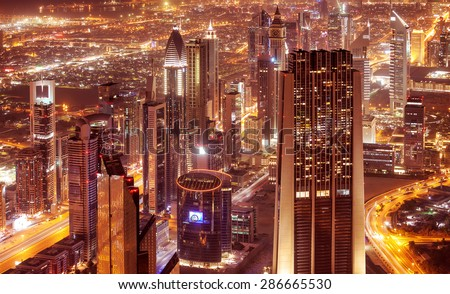Dubai city at night, beautiful modern buildings glowing lights, bird eye view on gorgeous cityscape, famous business and travel destination, United Arab Emirates - stock photo