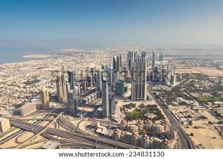 Dubai cityscape from Burj Khalifa at sunny morning, United Arab Emirates. - stock photo