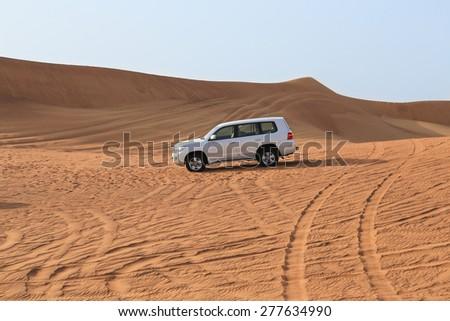 DUBAI, Desert - April 2015: Jeep driving on the desert near Dubai on April 27, 2015 in Dubai - stock photo