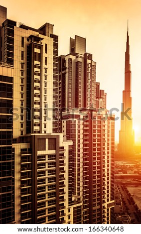 Dubai downtown in sunset, UAE, beautiful tall buildings in bright yellow sun light, burj khalifa, business center, luxury travel and tourism concept - stock photo