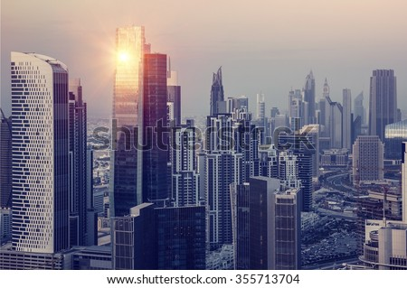 Dubai downtown in the evening, luxury modern buildings in bright yellow sunset light, futuristic cityscape of United Arab Emirates - stock photo
