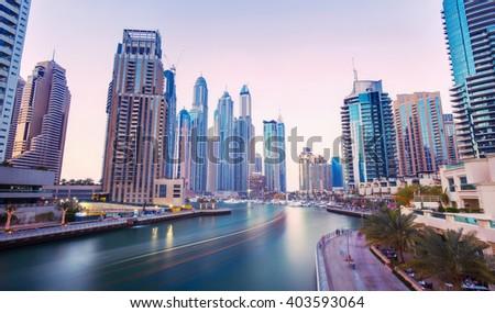 DUBAI FINANCIAL CENTER,UNITED ARAB EMIRATES-MARCH 11, 2016: Promenade in luxury Dubai Marina with modern skyscrapers in the evening,Dubai,United Arab Emirates - stock photo