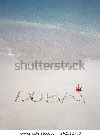 Dubai handwritten in sand with red flower - stock photo