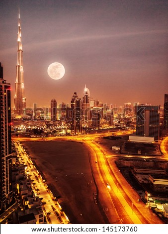 Dubai in moonlight, UAE, full moon, night scape in Dubai downtown, modern Arabian architecture, middle east, illuminated city at night, luxury vacation  - stock photo