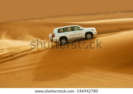 DUBAI - JUNE 2: Driving a 4-wheel drive on the desert, traditional entertainment for tourists on June 2, 2013 in Dubai - stock photo
