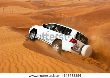 DUBAI - JUNE 2: Driving a 4-wheel drive SUV on the desert, traditional entertainment for tourists on June 2, 2013 in Dubai - stock photo