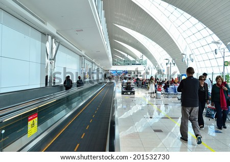 DUBAI - JUNE 20: Travellers in departure lounge of Dubai International Airport on June 20, 2014 in Dubai, UAE. This airport is the biggest in Middle East region.