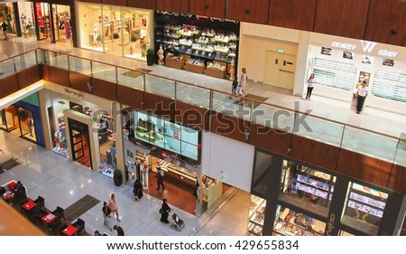 Dubai Mall, a top view of the inside, boutiques and shops, people walking and shopping, United Arab Emirates April 14, 2014 - stock photo