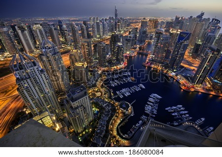 Dubai Marina at Blue hour, Glittering lights and tallest skyscrapers during a clear evening with Blue sky. - stock photo
