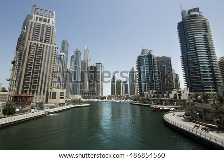 Dubai, marina bay at noon. Luxurious travel and holidays. Business and finance concept. Beautiful aerial shot of Dubai marina. Futuristic architecture. Hot summer day.  Aerial view.