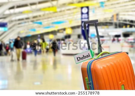 Dubai. Orange suitcase with label at airport. - stock photo