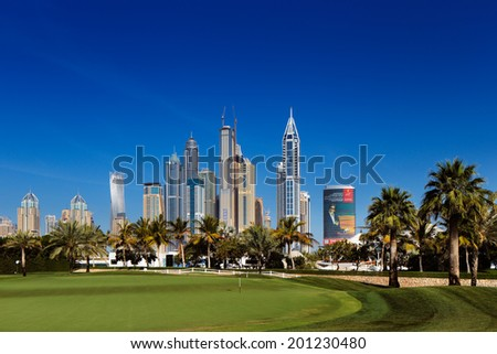 DUBAI, UAE - APR 15: A cityscape of Dubai Marina from a nearby lush green golf course on Apr 15, 2014 in Dubai, UAE. Dubai Marina is an artificial 3 km canal carved along the Persian Gulf shoreline - stock photo