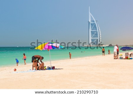 DUBAI, UAE - 2 APRIL 2014: People on the Jumeirah Beach in Dubai, UAE. Jumeirah Beach is a white sand beach that is located and named after the Jumeirah district of Dubai. - stock photo