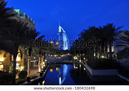 DUBAI, UAE-CIRCA JANUARY 2014: Night view of Burj al Arab hotel (7 star) from territory of Madinat Jumeirah hotel on evening circa January 2014 in Dubai, UAE. Madinat Jumeirah - luxury 5 star hotel  - stock photo