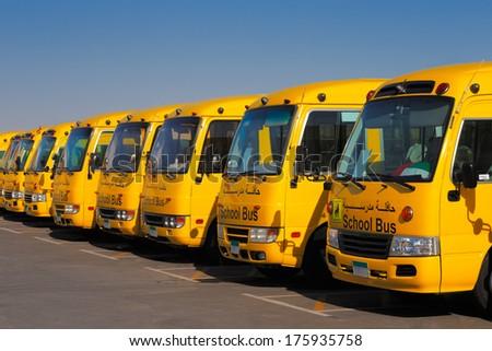 DUBAI, UAE - DEC 13: An oblique perspective of 8 yellow Arabic school busses on Dec 13, 2013 in Dubai, UAE.  - stock photo