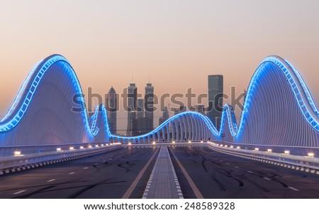 DUBAI, UAE - DEC 13: Wave shaped Meydan Bridge in Dubai blue illuminated at night. December 13, 2014 in Dubai, United Arab Emirates - stock photo