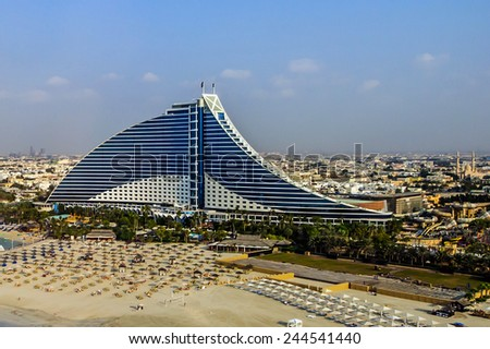 DUBAI, UAE - DECEMBER 25: Jumeirah Beach Hotel on December 25, 2014 in Dubai. This wave-shaped hotel complements the sail-shaped Burj Al Arab, which is adjacent to the Jumeirah Beach Hotel - stock photo