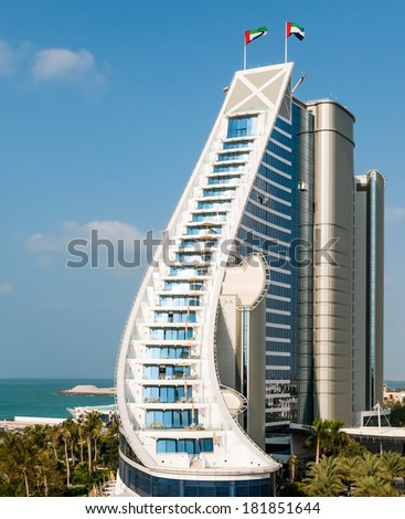 DUBAI, UAE - DECEMBER, 10, 2013: Jumeirah Beach Hotel, preceded by beachfront. Well-known for its wave-shaped silhouette, remains one of the best recognizable landmarks of Dubai, UAE - stock photo