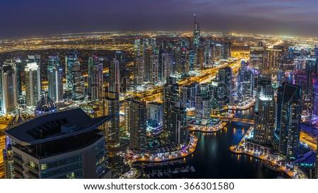 DUBAI, UAE - DECEMBER 14, 2015: Panoramic view of Dubai Marina district by night with numerous skyscrapers. Illuminated architecture of Dubai, United Arab Emirates. Scenic nighttime skyline. - stock photo