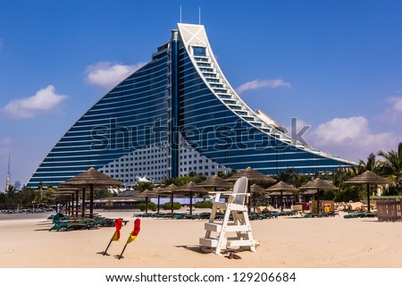 DUBAI, UAE - FEBRUARY 03: Jumeirah Beach Hotel, preceded by the beachfront, on February 3, 2013. Well-known for its wave-shaped silhouette, remains one of the best recognizable landmarks of Dubai, UAE - stock photo