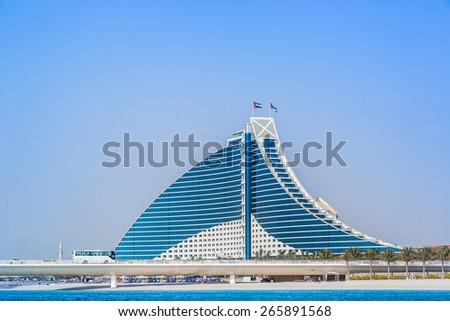 DUBAI, UAE - FEBRUARY 03: Jumeirah Beach Hotel, preceded by the luxury marina, on February 3, 2013. Wave-shaped resort, next to Burj Al Arab, remains one of the well-known landmarks of Dubai, UAE. - stock photo