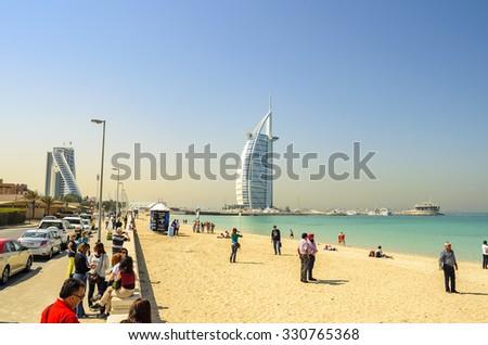 DUBAI UAE FEBRUARY 27 2014: Tourists and visitors admire the wonderful sea side part of Dubai near the famous Burj Al Arab hotel. - stock photo