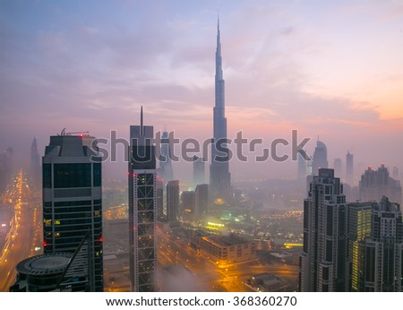 DUBAI, UAE - JANUARY 23, 2016: Burj khalifa, the highest building in the world, Downtown is covered by early morning fog on January,23 2016 in Dubai, United Arab Emirates - stock photo