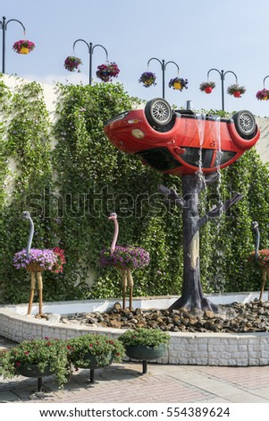 DUBAI, UAE - JANUARY 02, 2017: Dubai miracle garden: the world's largest natural flower garden.  The installation of the VW beetle on a tree in a fountain surrounded by ostriches
