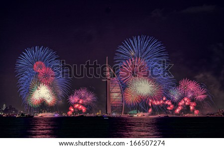 DUBAI, UAE - JANUARY 1: New year celebration with fireworks in Burj Al Arab and Burj Khalifa on January 1,2013 in Dubai, UAE - stock photo