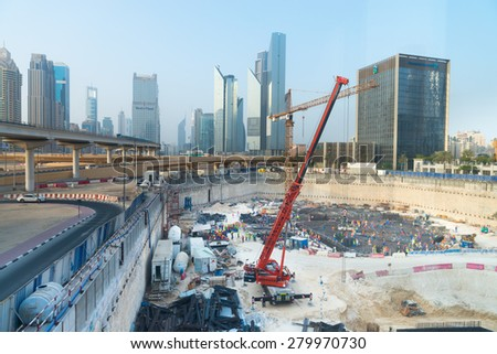 DUBAI, UAE - 16 JULY 2014: Cranes moving materials inside the foundation works of a Massive construction project in downtown Dubai. - stock photo