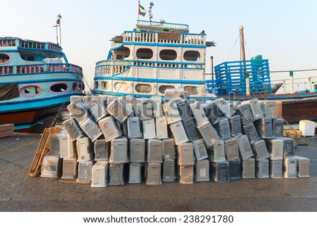 DUBAI, UAE - 16 JULY 2014: Dubai Creek port with moored up traditional dhows wooden boats and goods on the pier, United Arab Emirates  - stock photo
