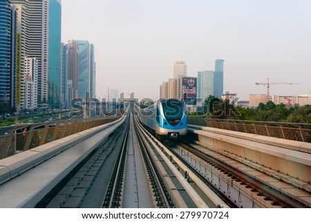 DUBAI, UAE - 16 JULY 2014: Passenger train cruising along Dubai's ultra-modern, high-tech metro transit rail system, with contemporary highrise buildings on either side. - stock photo