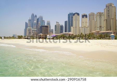 DUBAI ,UAE JUNE 15 : dubai beach with buildings in the background. this city is growing, and the contrast between nature and civilization is remarkable