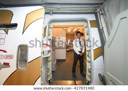 DUBAI, UAE - MARCH 09, 2016: Emirates crew member meet passengers on board of Boeing 777. Emirates is one of two flag carriers of the UAE along with Etihad Airways and is based in Dubai. - stock photo