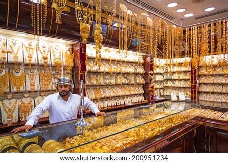 "DUBAI, UAE - MARCH 31: Gold on the famous ""Golden souk"" in Dubai Deira market on 31 March 2014, UAE. Deira is an old commercial center of Dubai with the biggest street market. - stock photo"