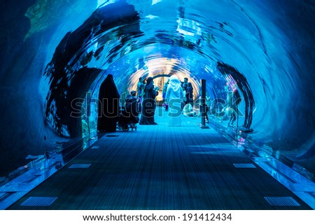 DUBAI, UAE - MARCH 28, 2014: People walking inside the Oceanarium tunnel iat Dubai Mall. At over 12 million sq ft, it is the world's largest shopping mall. - stock photo