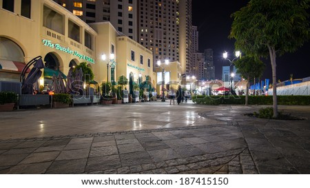 DUBAI, UAE - MARCH 27, 2014: People walking on The Walk (Jumeirah Beach Residence). The Walk is a 1.7 kilometer strip at ground level of the Jumeirah Beach Residence complex opened officially in 2008. - stock photo