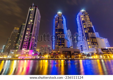 DUBAI, UAE - 31 MARCH 2014: Skyscrapers of Dubai Marina at night, UAE. Dubai Marina is a district in Dubai with artificial canal city who accommodates more than 120,000 people at Persian Gulf. - stock photo