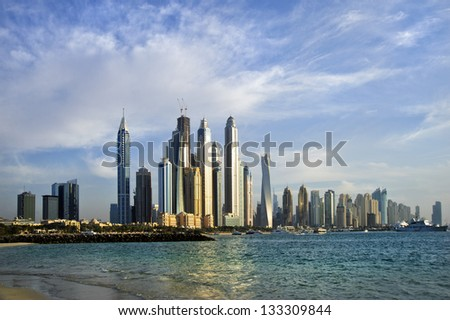 DUBAI, UAE -MARCH 23: View of modern skyscrapers in Dubai Marina on March 23, 2013 in Dubai, UAE. Dubai Marina - artificial canal city, carved along a 3 km stretch of Persian Gulf shoreline. - stock photo