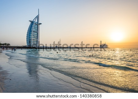 DUBAI, UAE - MAY 3: Burj Al Arab hotel during sunset on May 3, 2013 in Dubai. Burj Al Arab is a luxury 5 stars hotel built on an artificial island in front of Jumeirah beach. - stock photo