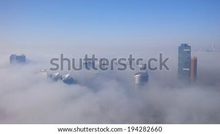DUBAI, UAE - MAY 12: Dubai Media City and Dubai Marina is covered by early morning fog on May 12,2013 in Dubai, UAE - stock photo