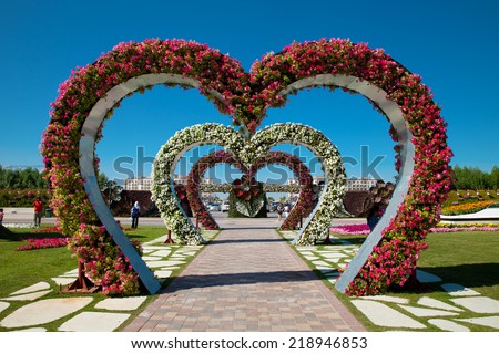 Dubai, UAE - Nov. 29, 2014: Heart shaped flower beds at the Alley of Hearts. Dubai Miracle Garden is famous for its extraordinary flower installations. A couple of people walking around at the park.