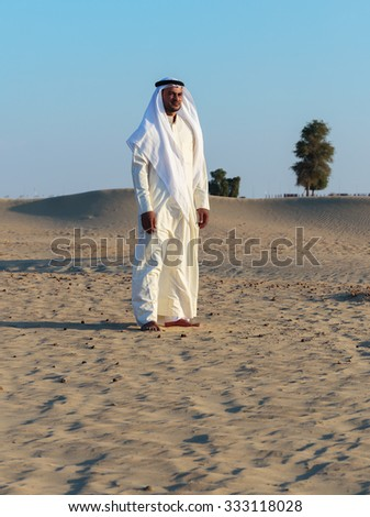 DUBAI, UAE-NOVEMBER 12, 2013: Arab man in desert at sunset
