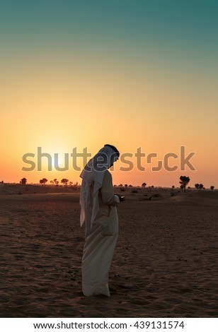 DUBAI, UAE - NOVEMBER 12, 2013: Arab man stands alone in the desert and watching the sunset
