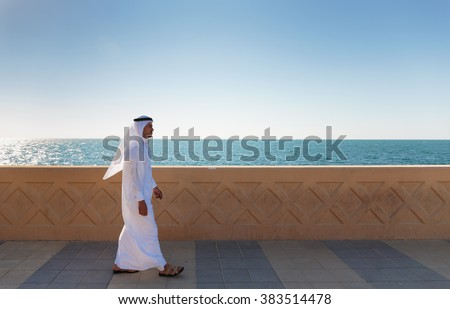DUBAI, UAE - NOVEMBER 7, 2013: Arabic man walking along the waterfront