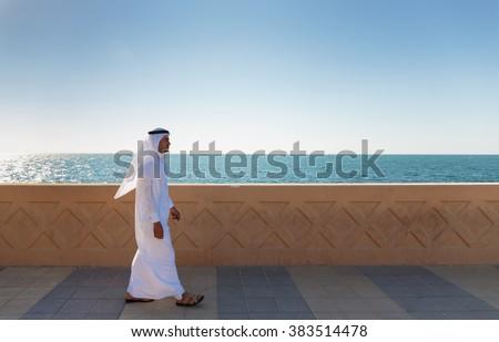 DUBAI, UAE - NOVEMBER 7, 2013: Arabic man walking along the waterfront - stock photo